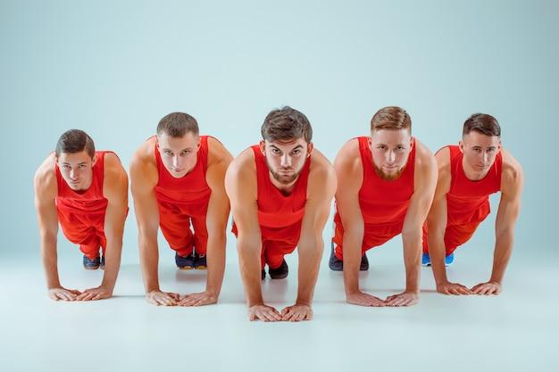 Die gruppe der gymnastischen akrobatischen kaukasischen männer im gleichgewicht posiert