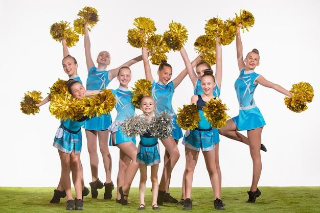 Die gruppe der jugendlichen cheerleader, die aufwerfen