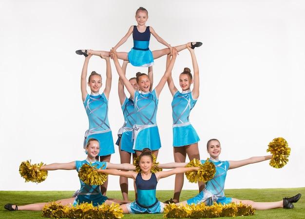 Die gruppe der jugendlichen cheerleader, die im weißen studio aufwerfen