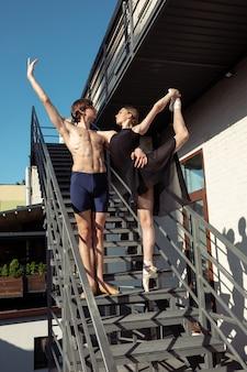 Die gruppe der modernen balletttänzer, die auf der treppe in der stadt auftreten