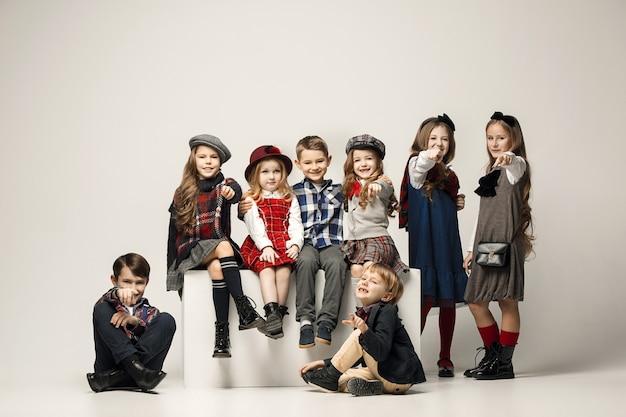 Die gruppe der schönen mädchen und jungen an einer pastellwand
