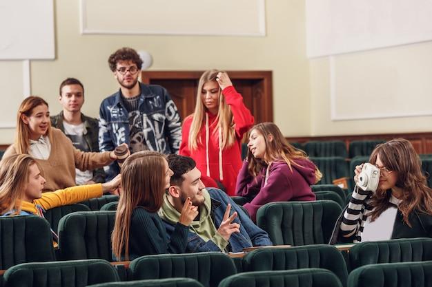 Die gruppe fröhlicher studenten, die vor dem unterricht in einem hörsaal sitzen.