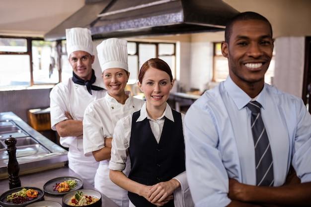 Die gruppe hotelpersonal, die mit den armen steht, kreuzte in der küche
