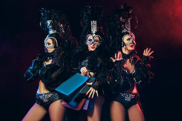 Die gruppe junger glücklich lächelnder schöner tänzerinnen mit karnevalskleidern, die mit einkaufstüten auf schwarzem studiohintergrund posieren