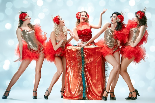 Die gruppe junger glücklicher lächelnder schöner tänzerinnen mit karnevalskleidern, die mit großem geschenk auf blauem studiohintergrund posieren