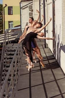 Die gruppe moderner balletttänzer, die auf der treppe in der stadt auftreten. schnelle bewegung des stadtlebens, anmut in den täglichen dingen. anmutige und flexible modelle bei sonnenschein mit gebäuden im hintergrund.