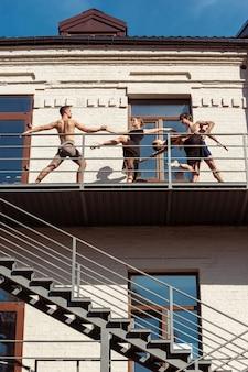 Die gruppe moderner balletttänzer, die auf der treppe in der stadt auftreten