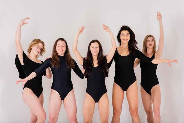 Die gruppe moderner balletttänzer im schwarzen body im weißen studio