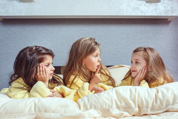 Die gruppe von freundinnen, die sich zeit fürs bett nehmen. glückliches lachendes kindergirsl, das auf weißem bett im schlafzimmer spielt. kinder in gelben frotteekleidern
