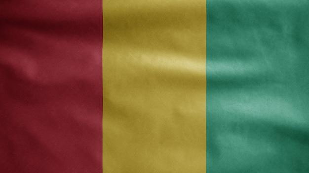 Die guineische flagge weht im wind. nahaufnahme von guinea banner weht, weiche und glatte seide. stoff textur fähnrich hintergrund. verwenden sie es für das konzept für nationalfeiertage und länderanlässe.