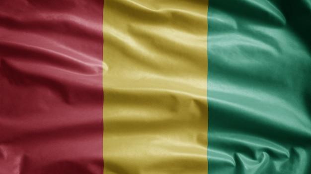 Die guineische flagge weht im wind. nahaufnahme von guinea banner weht, weiche und glatte seide. stoff textur fähnrich hintergrund