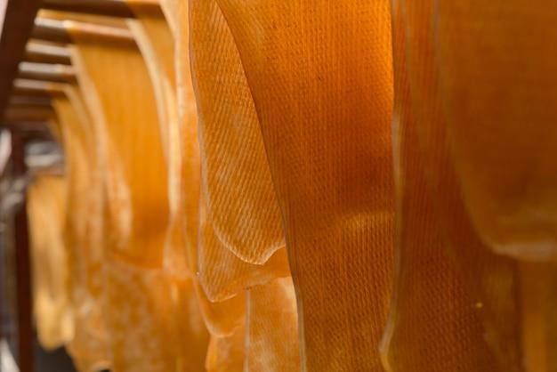 Die gummiblätter werden an einem bügel aufgehängt. gummiproduktion, backprozess.