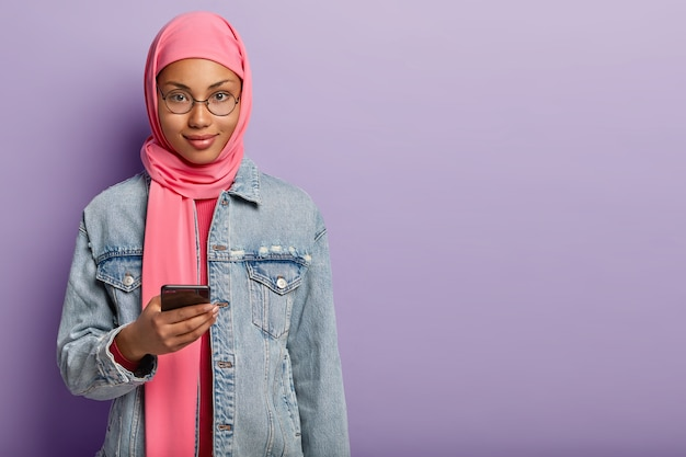 Die gut aussehende dunkelhäutige frau mit ansprechendem aussehen trägt einen rosa hijab und einen jeansmantel, hält ein modernes handy, wartet auf einen wichtigen anruf und steht über einer lila wand mit leerzeichen