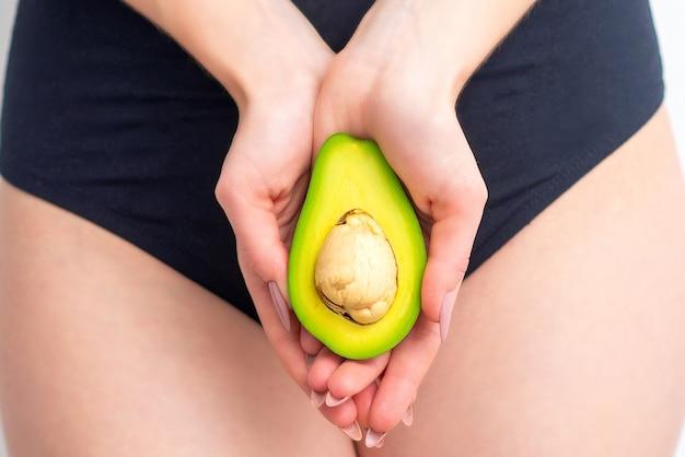 Die hälfte der avocado in weiblichen händen schließen. schönheits- und hautpflegekonzept.