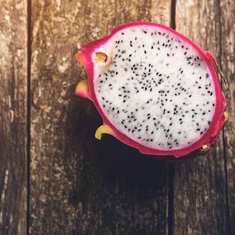 Die hälfte der drachenfrucht auf rustikalem holzhintergrund. pitaya oder drachenfrucht. exotische tropische früchte.