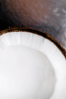 Die hälfte der frischen kokosnuss liegt auf dem tisch