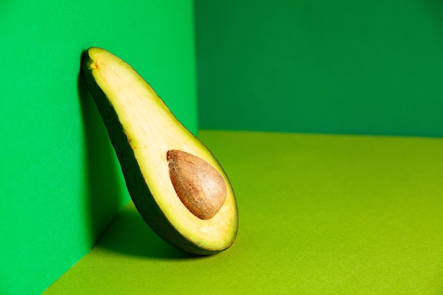 Die hälfte der frischen leckeren reifen gesunden avocado mit samen lehnte sich an die grüne wand