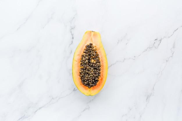 Die hälfte der frischen papaya auf einem weißen marmor