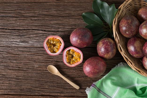 Die hälfte der passionsfrucht und bio-passionsfrucht auf holzkorb