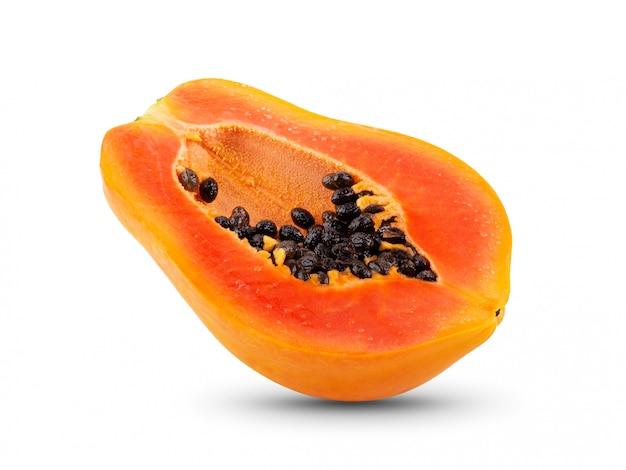 Die hälfte der reifen papaya-frucht mit samen an der weißen wand.