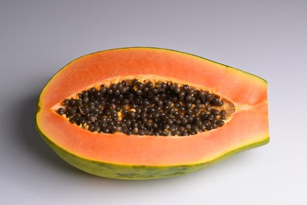 Die hälfte der reifen papaya-frucht mit samen isoliert auf weißem hintergrund voller schärfentiefe