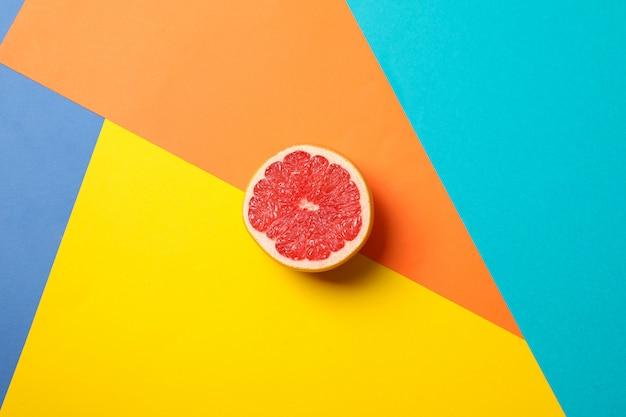 Die hälfte der saftigen grapefruit auf mehrfarbigem hintergrund, platz für text