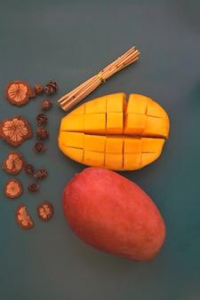 Die hälfte der taiwan-mango mit gelbem fruchtfleisch und roten schalenfrüchten neben drideblumen auf dem hintergrund