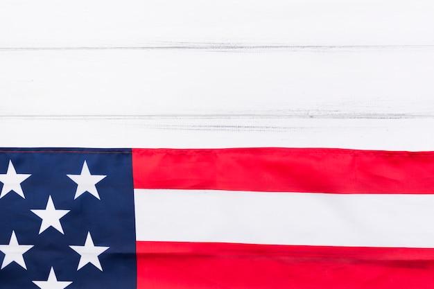 Die hälfte der usa-flagge und die hälfte des weißen holztischs