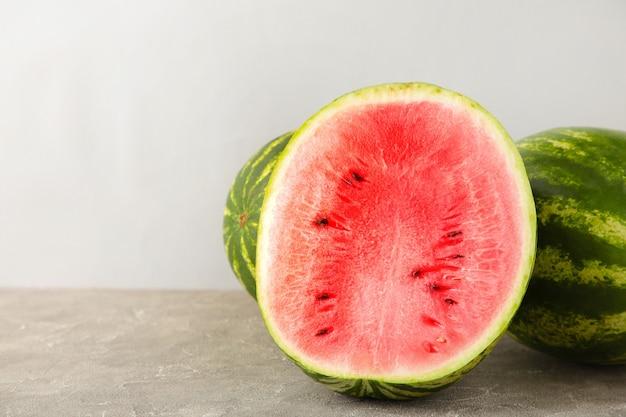 Die hälfte der wassermelone auf grauem hintergrund