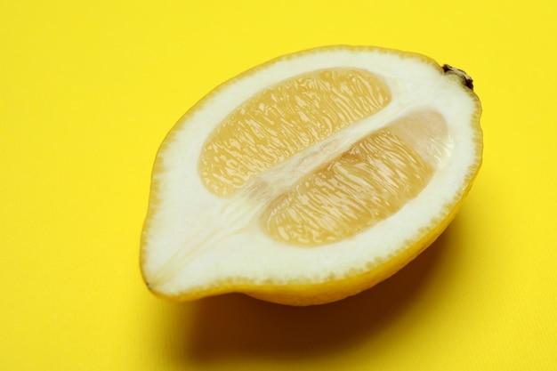 Die hälfte der zitrone auf gelb, nahaufnahme