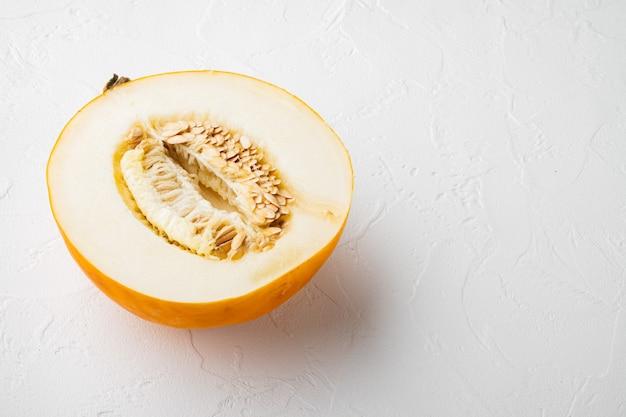 Die hälfte des cantaloupe-melonen-sets auf weißem steintischhintergrund mit kopienraum für text
