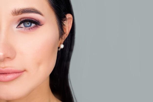 Die hälfte des gesichts des modells links vom textbereich, nahaufnahme-augen-make-up. ein konzeptfoto für werbekosmetik oder maskenbildnerdienste.