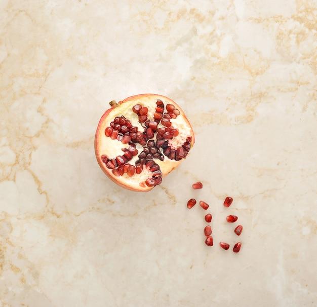 Die hälfte des granatapfels auf marmor