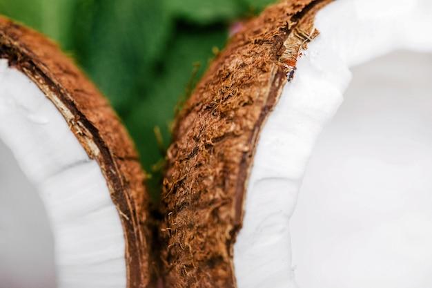 Die hälfte einer kokosnuss liegt auf grünen blättern