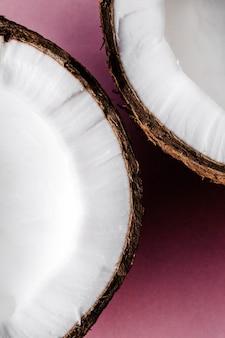 Die hälfte einer kokosnuss liegt auf rosa hintergrund