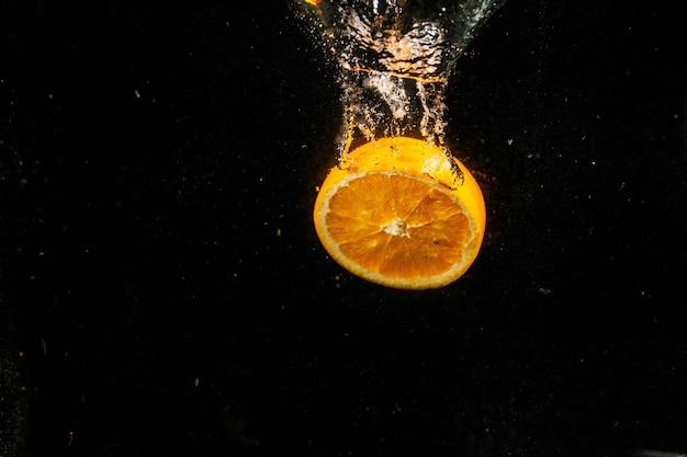 Die hälfte einer orange fällt auf schwarzem hintergrund