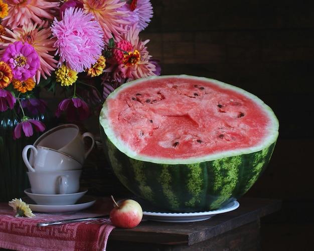 Die hälfte eines geschnittenen reifen wassermelonenfragments eines stilllebens mit blumen und geschirr auf dem tisch