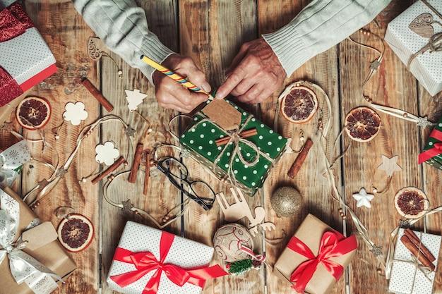 Die hände älterer älterer männer unterschreiben weihnachtsgeschenke auf tisch mit ch