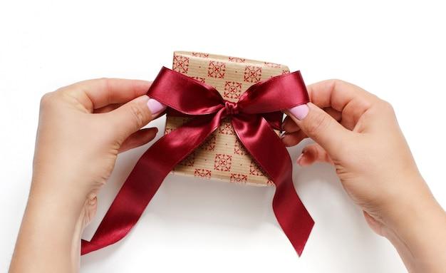 Die hände binden eine schleife an ein ecru-geschenkbox-isolat