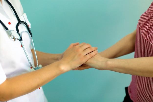 Die hände der ärztin, welche die hand des patienten für ermutigung und empathie halten. partnerschaft, vertrauen und medizinisches ethikkonzept.