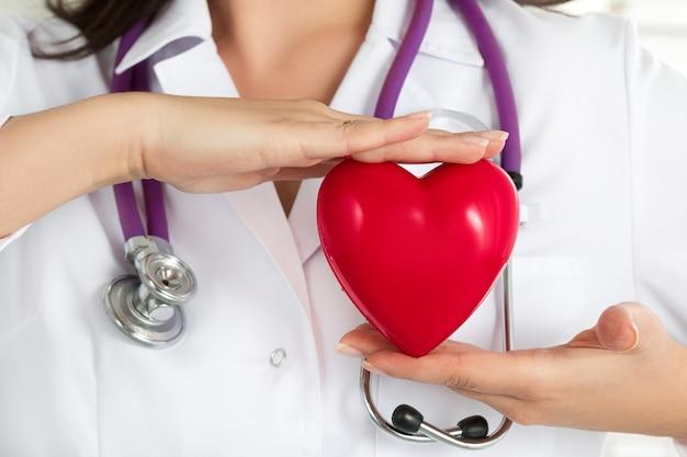 Die hände der ärztinnen halten rotes herz vor ihrer brust. nahaufnahme der hand des doktors. medizinische hilfe, prophylaxe oder versicherungskonzept.
