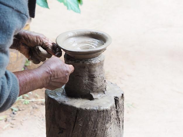 Die hände der alten frau formen lehmtonwaren auf hölzernem stand.