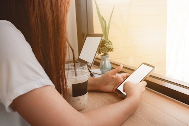 Die hände der asiatin, die handy und laptop mit weißem schirm im kaffeecafé halten.