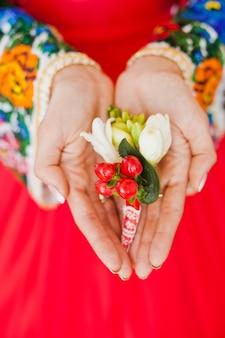 Die hände der braut halten den boutonniere ihres bräutigams
