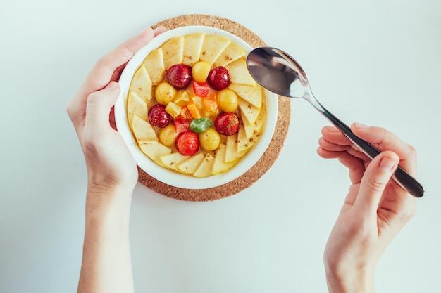 Die hände der draufsichtfrau, die morgenbrei mit äpfeln, kirschen und kandierten früchten auf weißem hintergrund essen