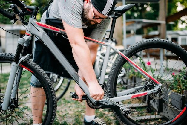 Die hände der fahrradmechaniker stellen die fahrradpedale ein