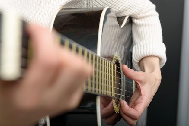 Die hände der frau, die akustikgitarre, abschluss oben spielen