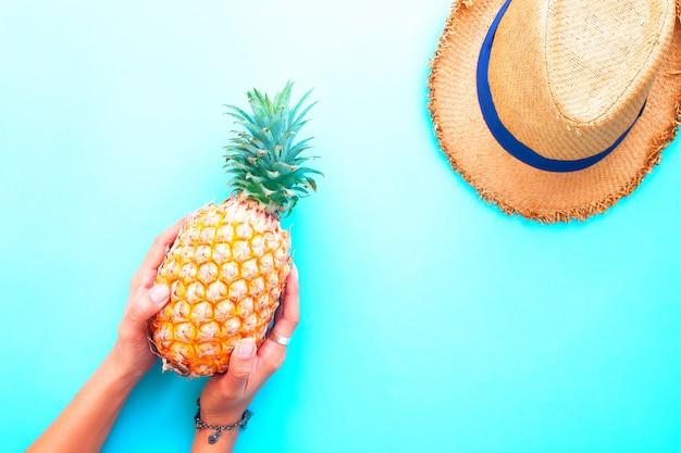 Die hände der frau, die ananas mit strohhut auf blauem farbhintergrund halten