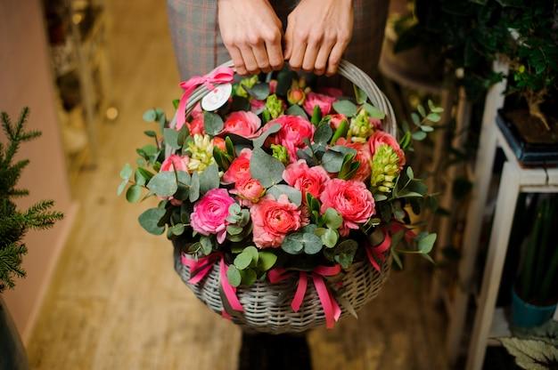 Die hände der frau, die einen großen weidenkorb mit blumen für den valentinstag halten