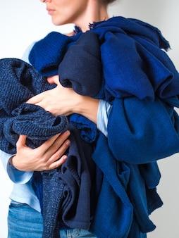Die hände der frau, die einen stapel der weichen warmen strickenden kleidung der blauen farbstrickjacken halten.